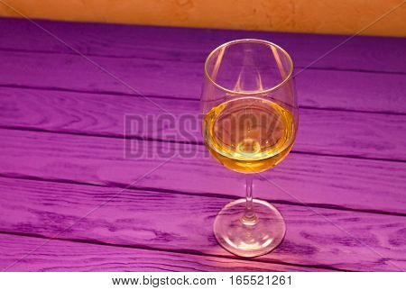 White wine in the wineglass on the purple wood background