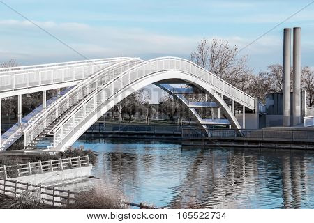 Beautiful modern white iron bridge over artificial river at a park