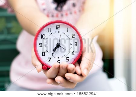 Holding red clock on hand and giving this to you with garden background.