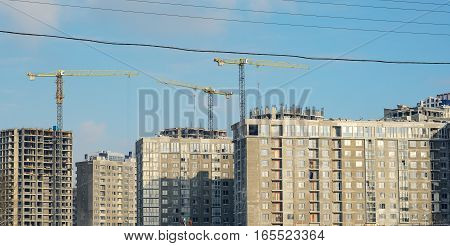 Panorama to the construction site. Building under construction and three troitelnye cranes against the blue clear sky.