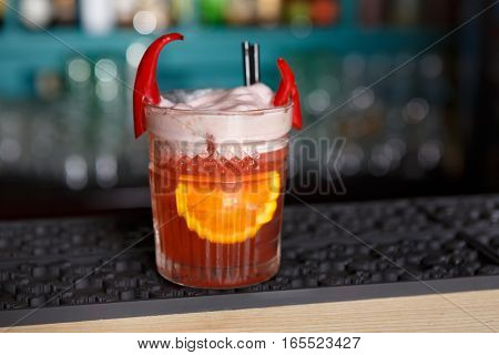 Closeup of frothy exotic spicy alcohol cocktail with chili peppers and orange in restaurant at bar background. Glass on bar table, original and creative refreshing drink.