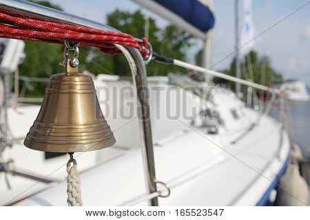 Bronze bell hanging on a yacht standing at the pier. Transport