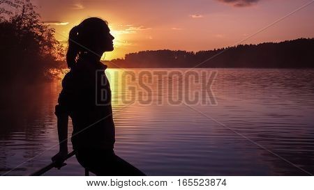 Silhouette of a girl on the background of the sun. Girl standing near water outdoors. Gold sunset lake. Young woman thinking about something river during golden sunset. Backlight photo shot