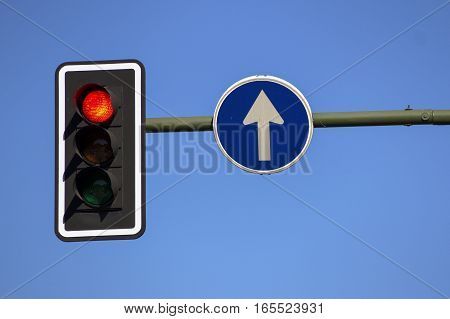 Red traffic light and single direction signal