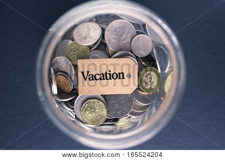 Saving Concept : Vacation label with coins in the glass