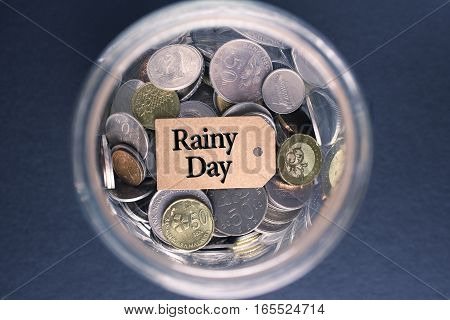 Saving Concept : Rainy Day label with coins in the glass
