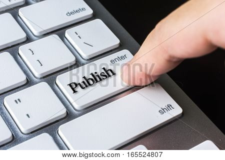 Finger on computer keyboard keys with Publish word