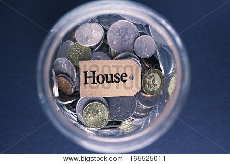 Saving Concept : House label with coins in the glass