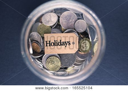 Saving Concept : Holidays label with coins in the glass