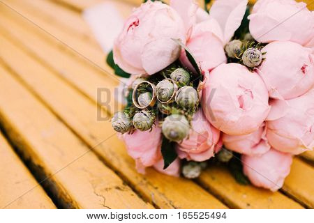Wedding rings on a bouquet of peonies