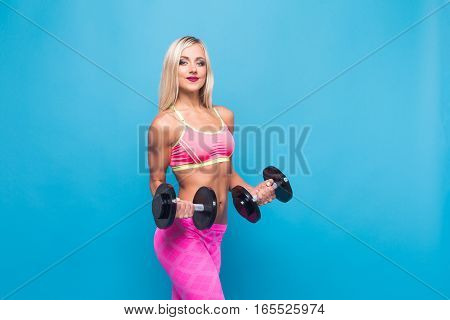 Portrait of attractive blonde woman in pink sportswear posing with dumbbells in arms on blue background