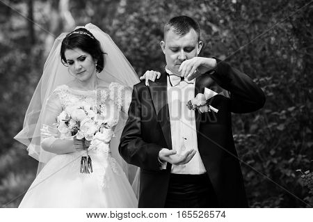 Wedding Couple Stay At Forest. Groom Throw Rings On Air. Black And White Photo