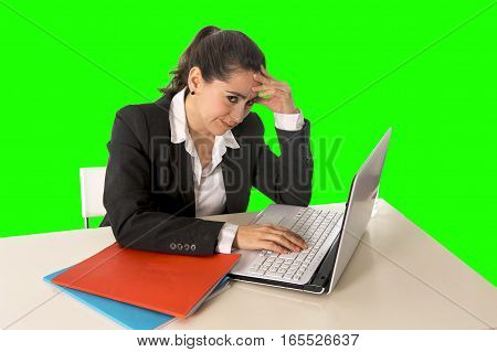 overworked hispanic business woman wearing business suit working on laptop computer looking stressed and worried in woman facing work problem concept isolated on green chroma key screen background