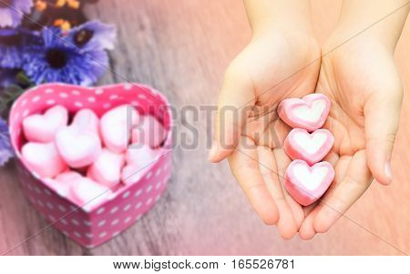 Valentine day concept close up pink Marshmallow preserve on hand on blurred background of pink Marshmallows in pink heart box on wooden table vintage tone