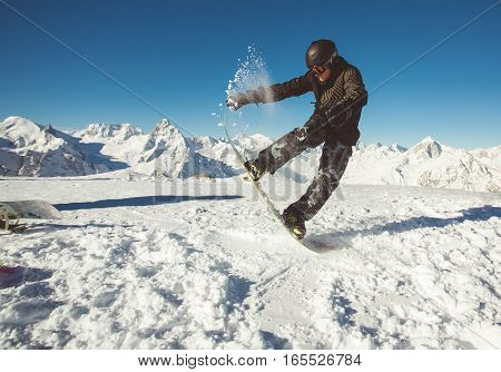 Young snowboarder jumping on slope with beautiful alpine mountain landscape - snowboarding concept.