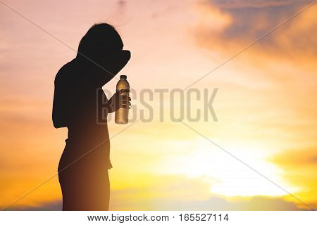 Silhouette of woman is drinking sport drink