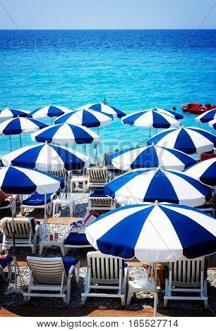 turquiose water of cote dAzur over beach umbrellas, Nice, France, retro toned