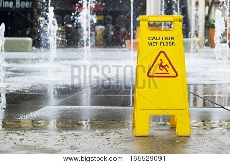 Wet floor sign at outdoor fountain of department store