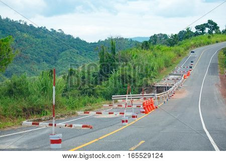 Damaged road with caution traffic sign in thailand