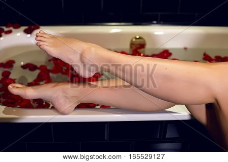 girls feet standing on the edge of the white tubs of water with petals