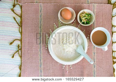 rice porridge rice gruel or congee with pork egg sliced ginger and vegetable delicious the traditional Chinese breakfast on wooden table and hot coffee