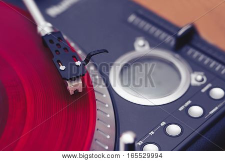 Turntable ripping red vinyl record with music