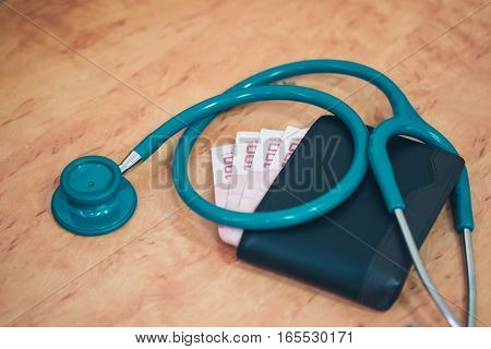 hecking an old wallet on a black table with a stethoscope.