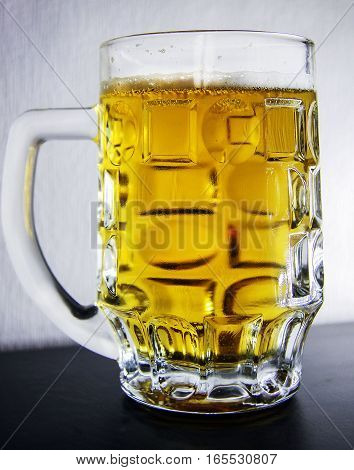 Glass with fresh beer on the table