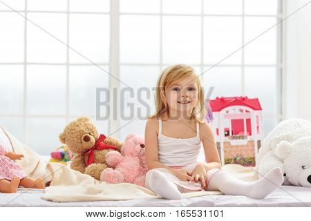 Happy little girl is sitting on bed near toys. She is looking at camera and smiling