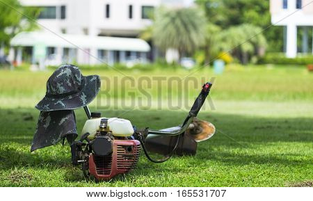 City gardener mowing lawn with gas trimmer