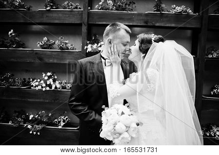 Beautiful Wedding Couple Stay Background Wall With Flowers On Pots. Black And White Photo