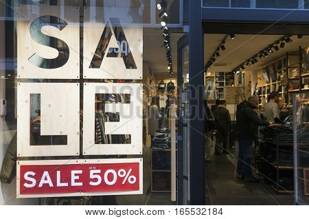 Utrecht, Netherlands, 14 january 2017: sale sign and discount number in display window of clothing store full of customers