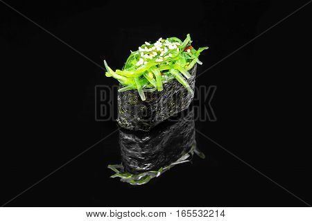 Gunkan spicy sushi with salad Chuka Hiashi on a black background with reflection