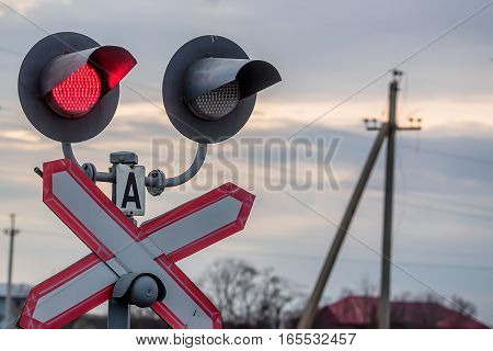 Railway red traffic light and crossing sign on sky background