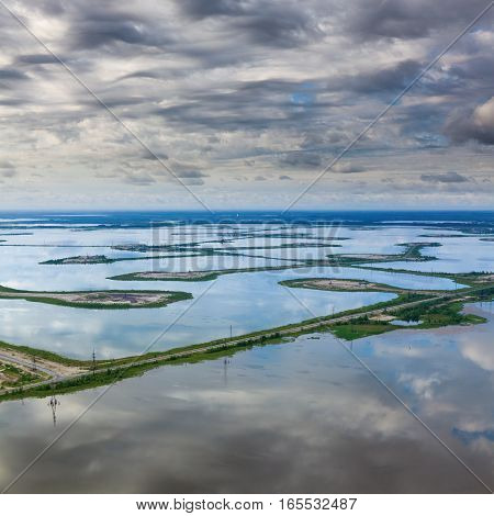 Aerial view of the calm lake that reflects the clouds. Oil field is located here. The road crosses the lake.