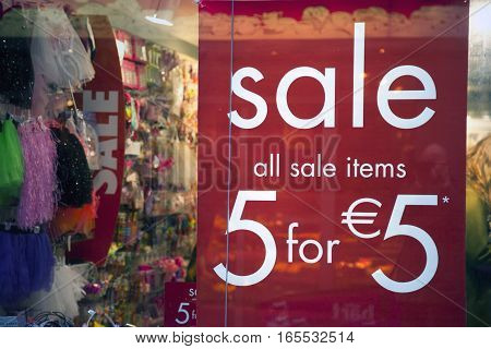 sale sign on shop window and colorfull items in full store