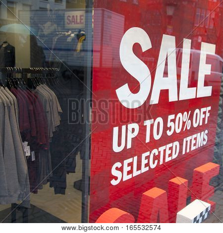 sale signs in display window of clothing store and sweaters and shirts in rack inside