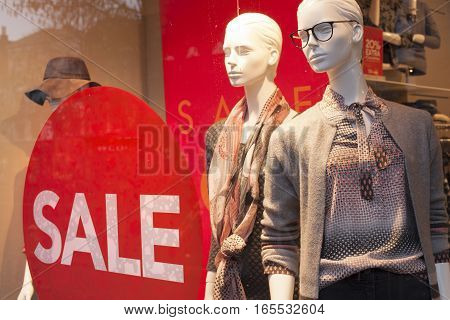 sale sign on shop window and fashion dolls in the store display clothes