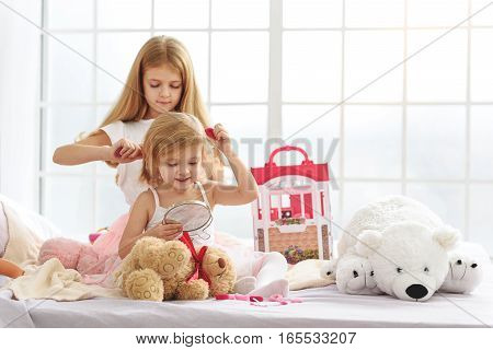 Pretty girl is combing hair of her little sister with love. Happy kid is smiling and giving her a scrunchy. They are sitting near toys in bedroom