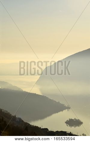 A suggestive view of Lake Iseo at sunset with the fog - Lombardy - Italy
