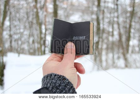 Discover  idea. Hand holding a book with the inscription. On the background of the forest with snow-covered trees