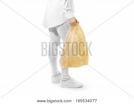 Blank yellow plastic bag mockup holding hand. Woman hold dark carrier sac mock up. Grey bagful branding template. Shopping carry package in persons arm. Promotional packet for logo branding.