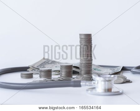 Stethoscope And Money Coin Stack On White Background. Money For Health Care, Financial Aid, Concept.