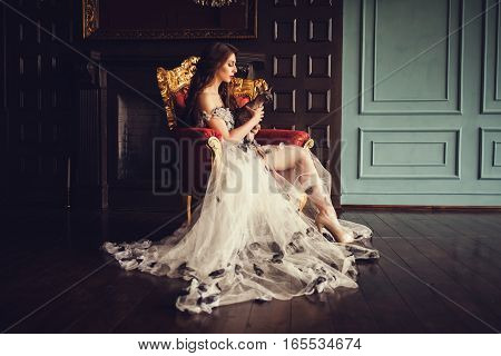 graceful lady sitting in a luxurious vintage chair with a cat