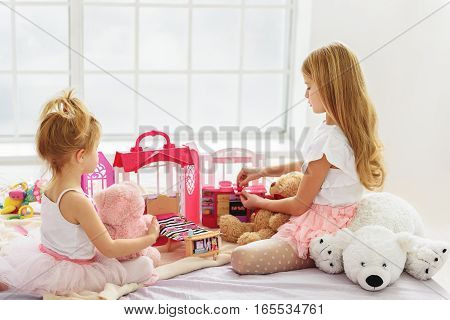 Pretty girls are enjoying game with small doll house. They are sitting on bed and holding teddy bears
