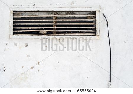 Rusty old ventilation grille in the wall with a wire. Old ragged plaster white