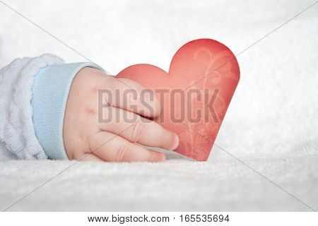 Red heart shaped card in baby hand on white soft blanket background
