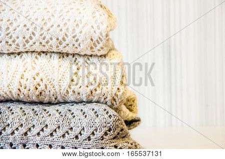 Stack of cozy knitted woolen clothes on the table. White, beige and grey sweater.