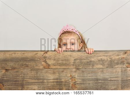 Joyful little child is peeking over wood fence with curiosity. She is looking at camera and smiling. Isolated on background