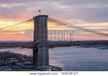 New York City colorful sunset landscape scene with the Brooklyn Bridge across the East River towards Manhattan